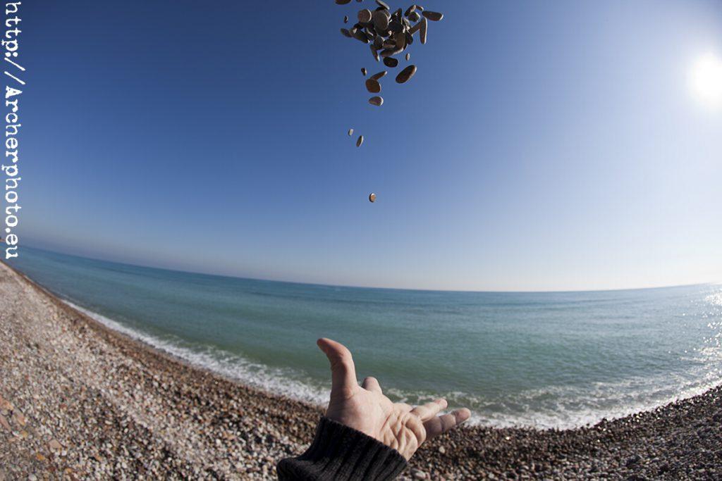 Una mano lanzando piedras al aire realizada con una lente ojo de pez por Archerphoto, fotografos Valencia.